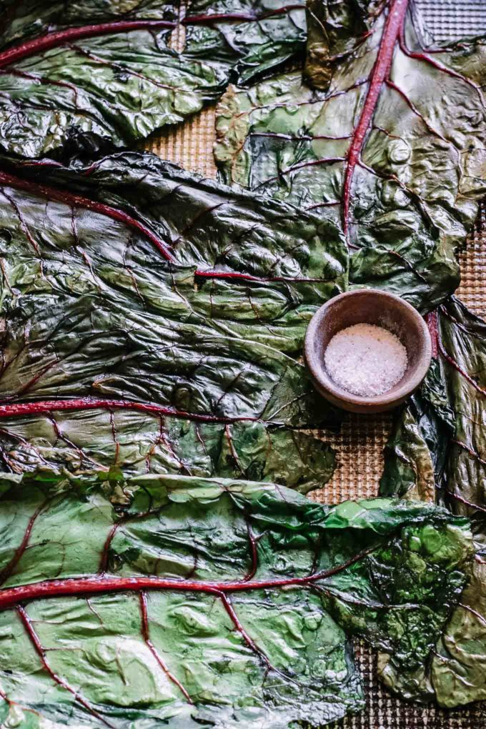 baked chard leaves on a sheet pan with salt