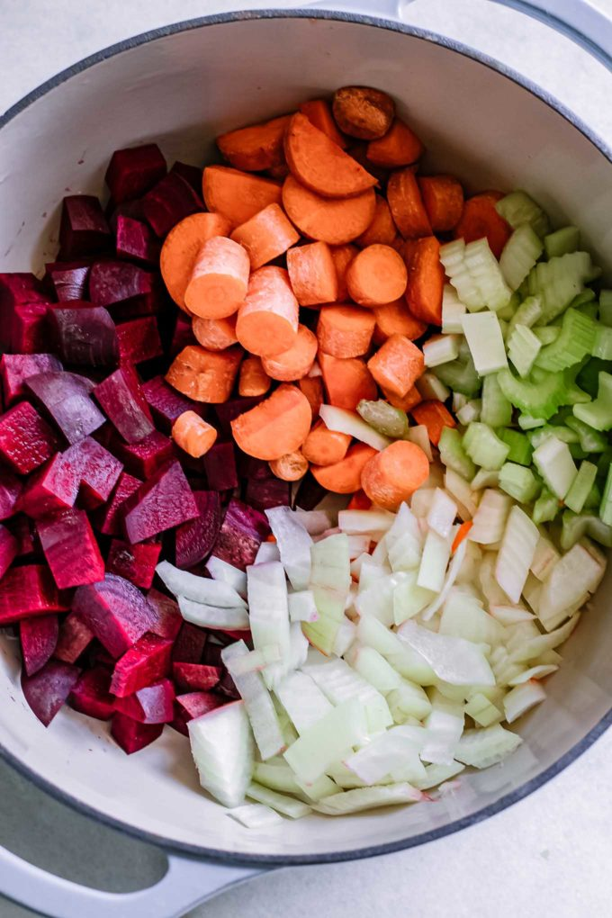 diced beets, carrots, celery, and onions in a soup pot