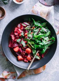 beet vegetable soup with chopped beet greens in a black bowl on a blue table