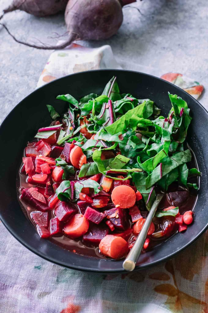 a bowl of beet vegetable soup on a blue table with beet greens