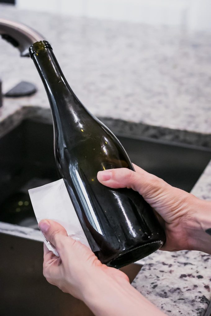 a hand peeling a label from a wine bottle