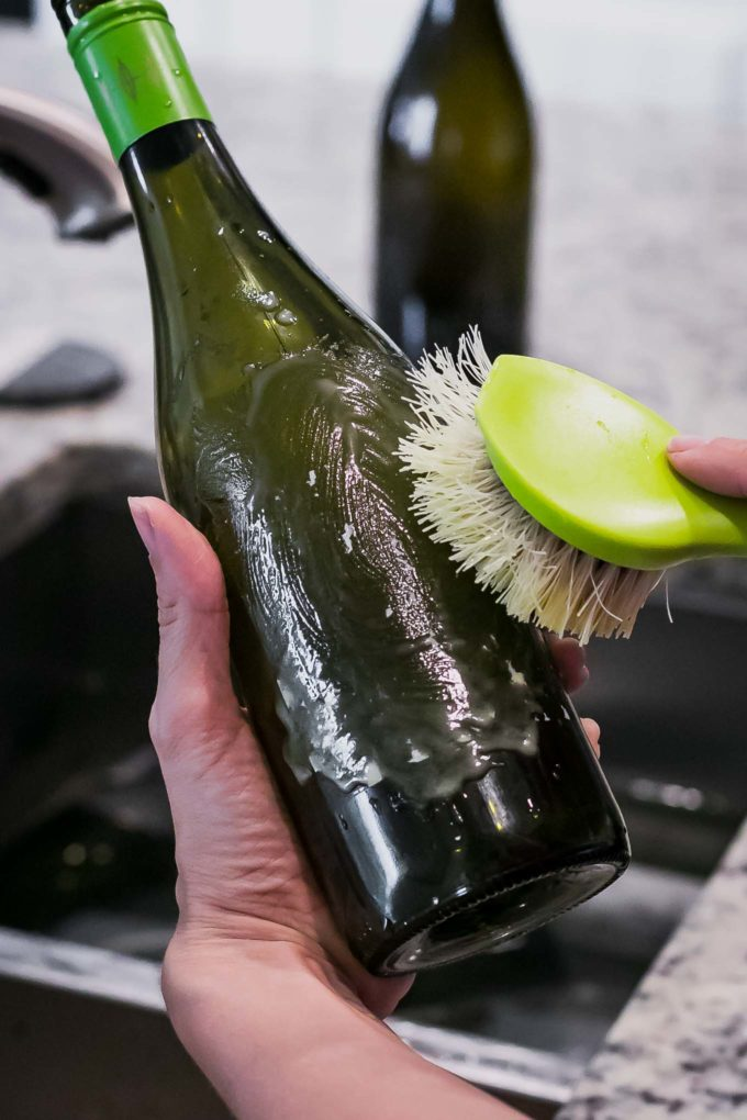 a hand scrubbing a label off a wine bottle with a wooden scrub brush