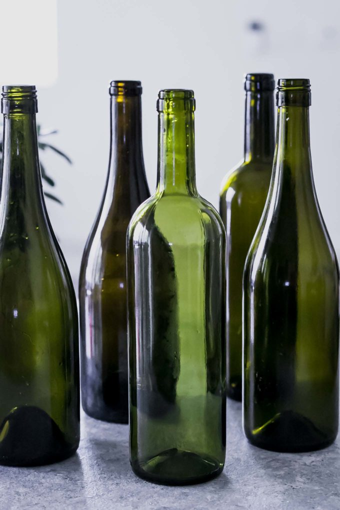 five wine bottles without labels on a white table