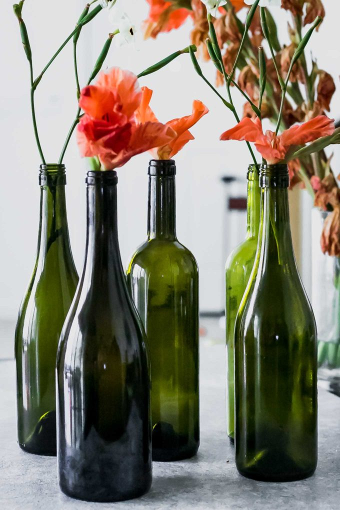 wine bottle flower vases with orange flowers on a white table