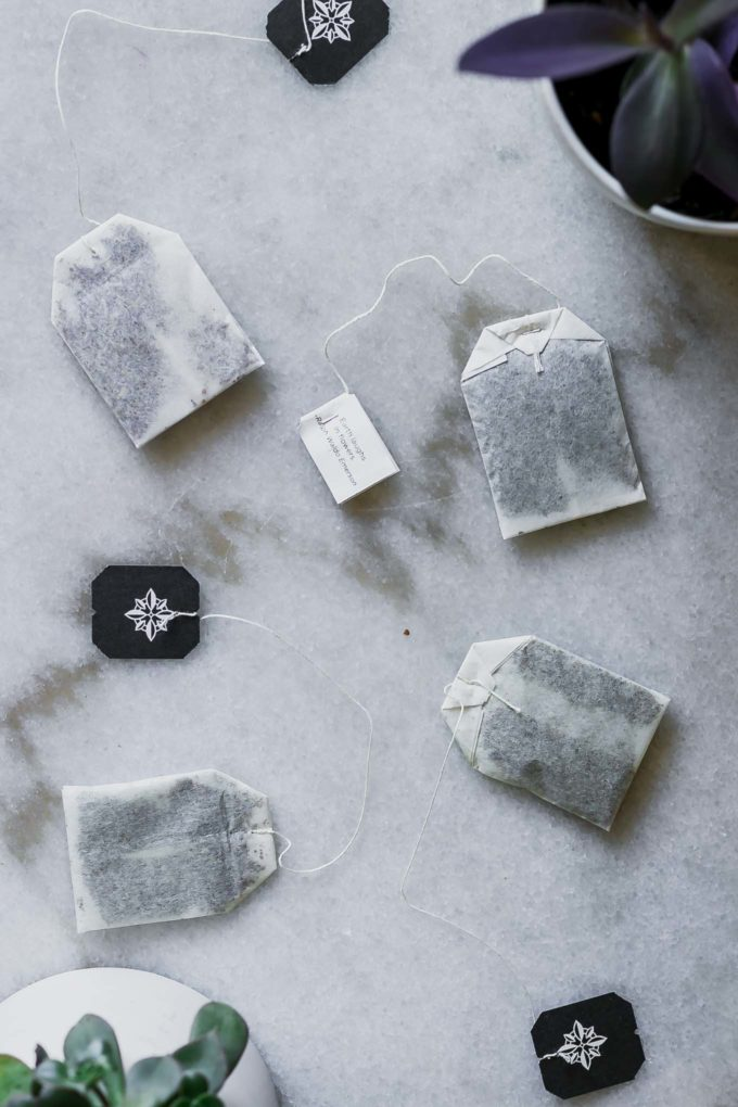 four tea bags and two succulent plants on a marble table
