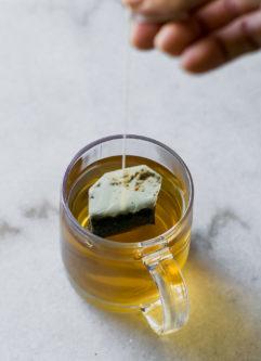 a hand pulling a tea bag out of a glass mug of brewed tea