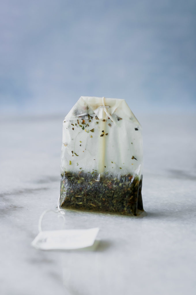 a used tea bag sealed with a metal clip on a marble table