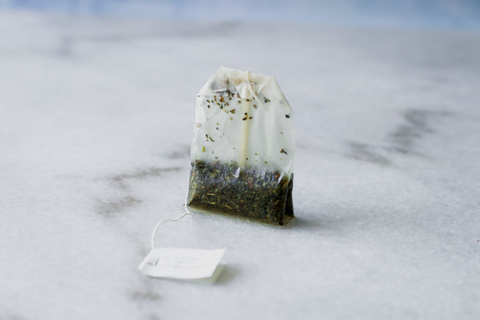 a used tea bag on a white marble countertop