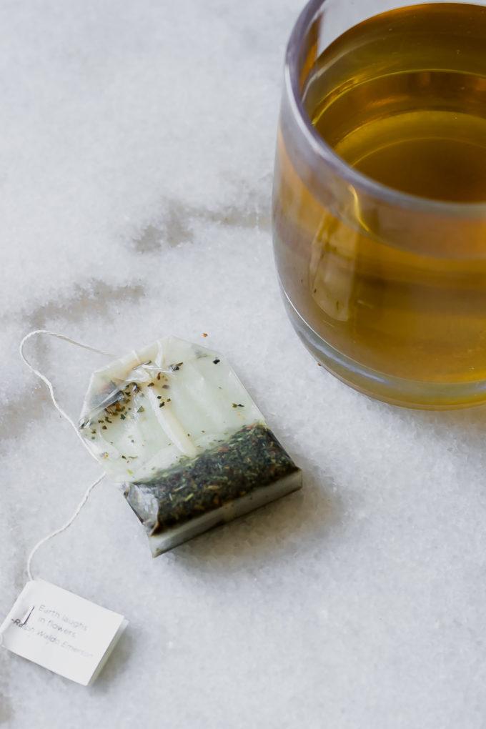 a used tea bag on a white table next to a mug of brewed tea