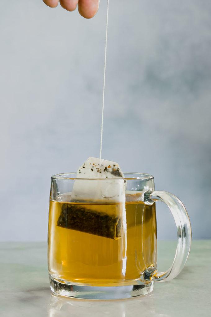 a hand pulling a tea bag out of a glass tea mug