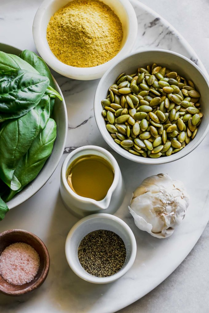 bowls of basil, pumpkin seeds, nutritional yeast, olive oil, salt, pepper, and a whole garlic clove on a white table