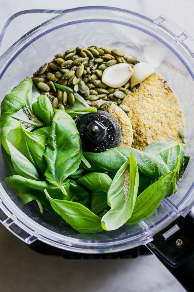 basil, pumpkin seeds, cheese, and garlic inside a food processor