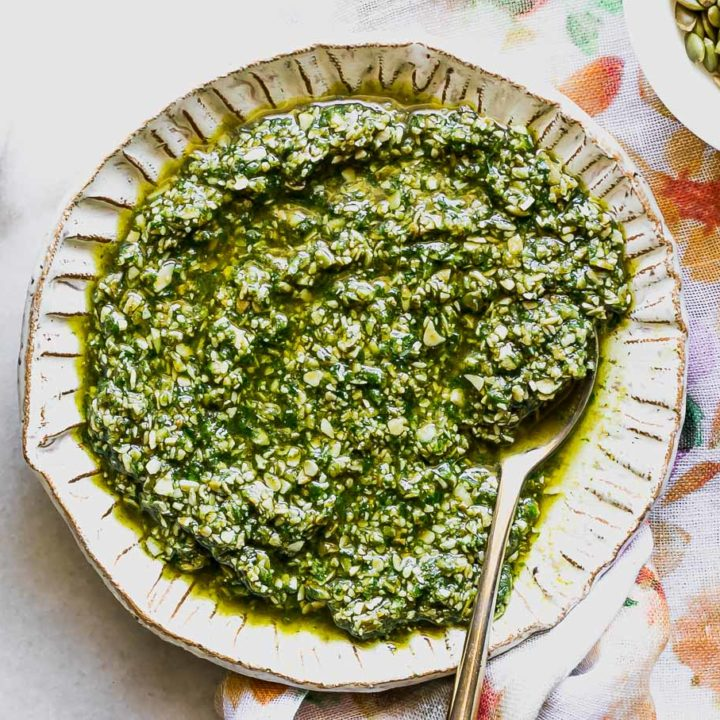 pumpkin seed pesto on a white plate on a white table with bowls of pumpkin seeds and salt