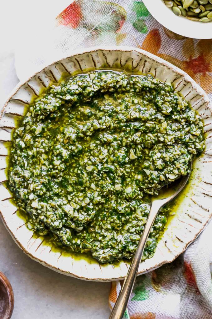 pumpkin seed pesto sauce in a white bowl with a gold fork