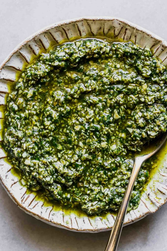 pumpkin pesto sauce on a gold plate on a white table