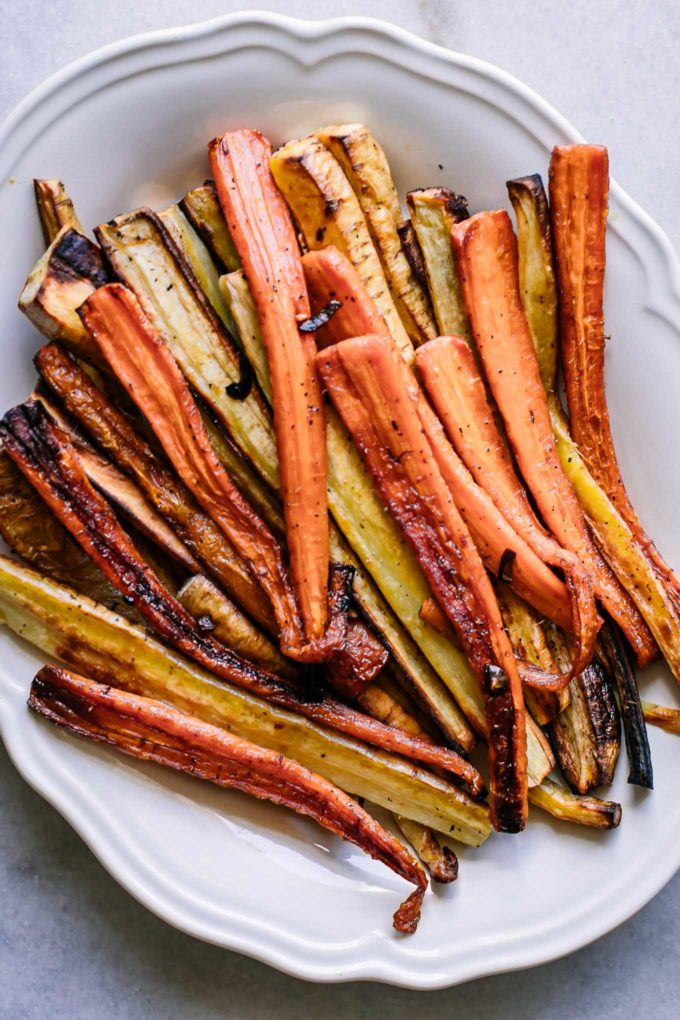 roasted carrot and parsnips on a white plate on a white table