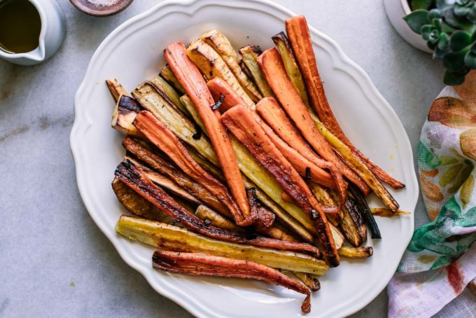 baked parsnip and carrot strips on a white plate on a marble table