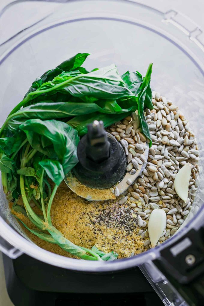 basil, sunflower seeds, cheese, and garlic in a food processor