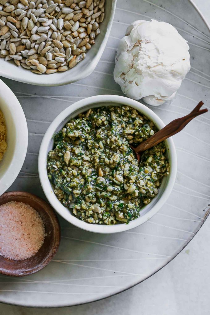 a plate with a bowl of sunflower seed pesto and a bowl of sunflower seeds