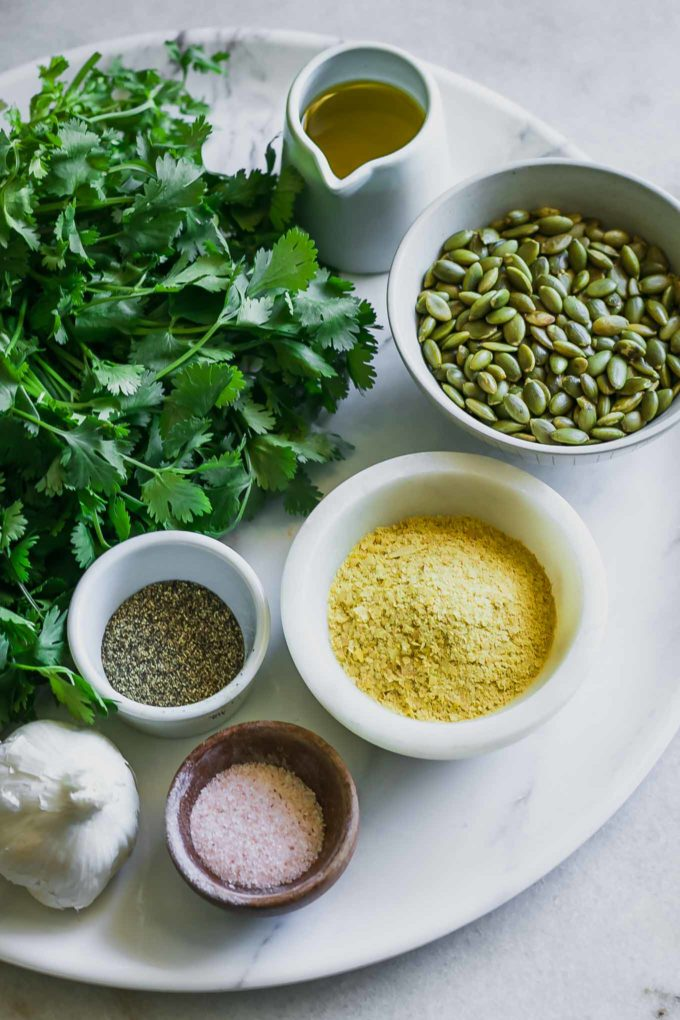 fresh cilantro and bowls of oil, seeds, nutritional yeast, salt, pepper, and garlic on a white table