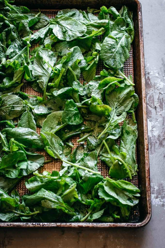 raw radish greens with oil and spices on a baking pan