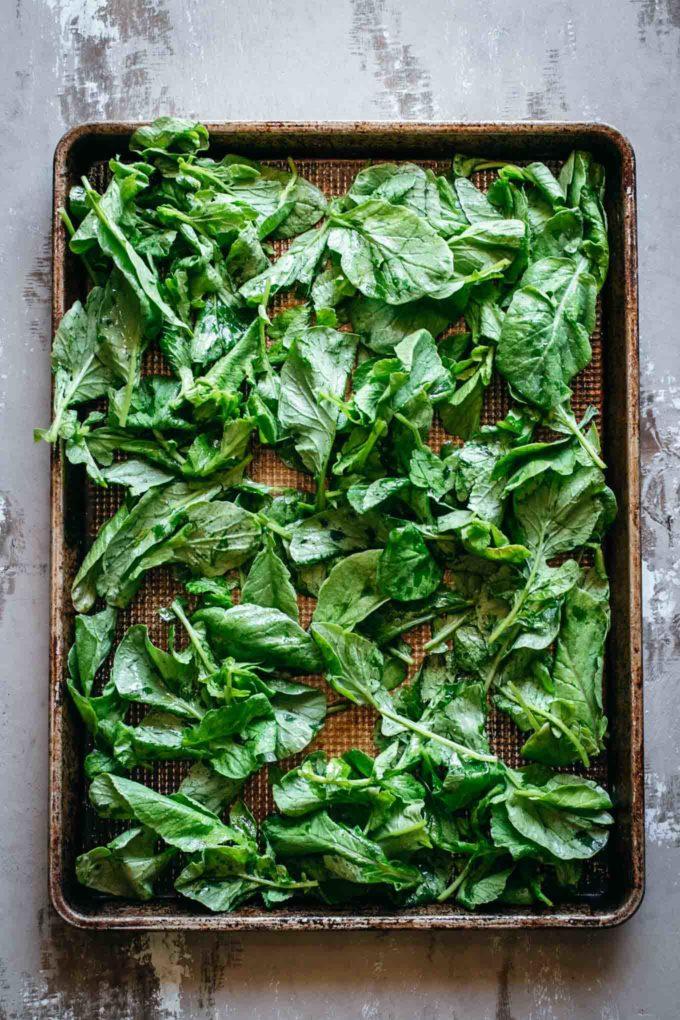 raw radish leaves on a baking pan