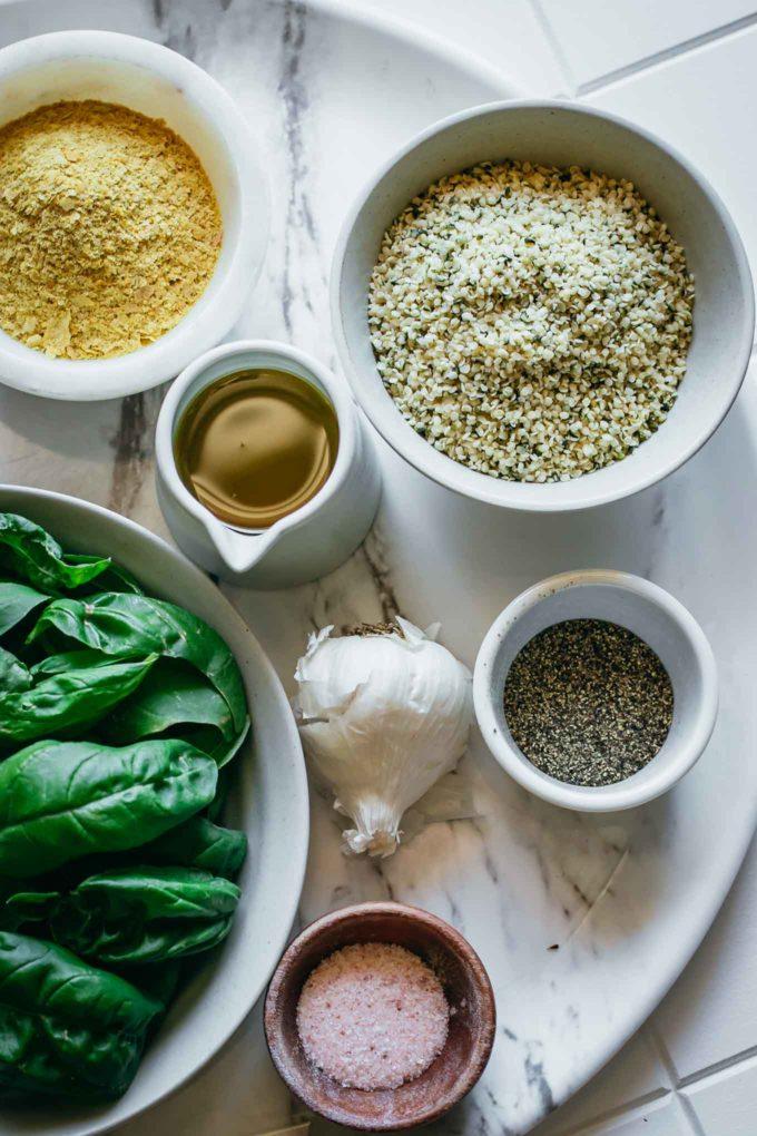 bowls of basil, cheese, oil, hemp seeds, salt, pepper, and garlic