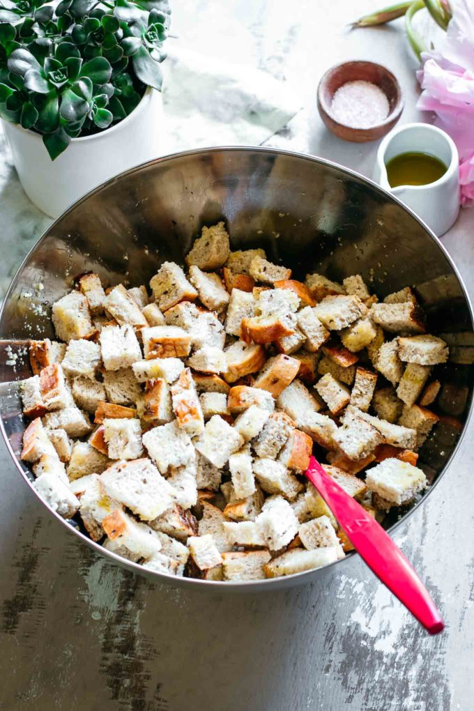 rye bread cubes in a mixing bowl with oil, salt, pepper, and a red spoon