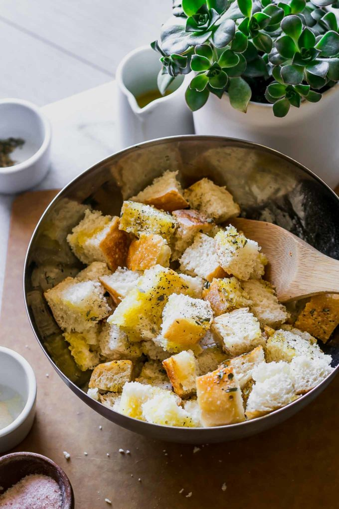 seasoned croutons in a metal bowl with a wooden spoon