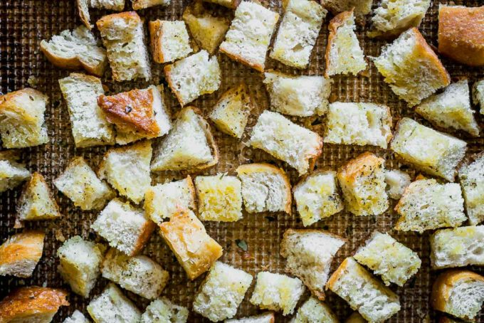 seasoned sourdough croutons on a baking sheet