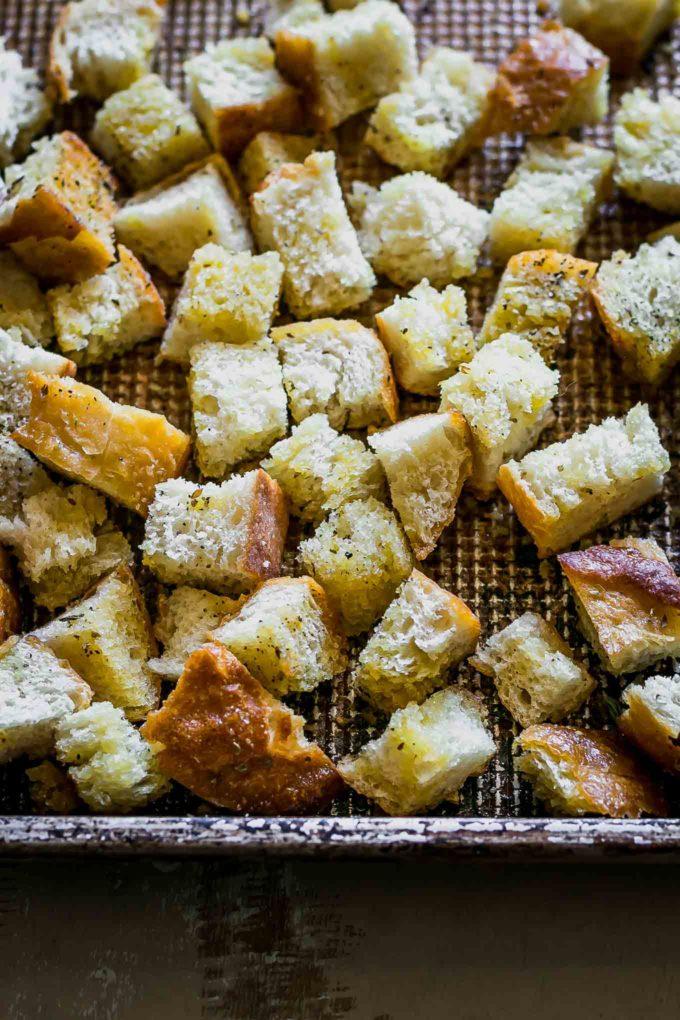 seasoned sourdough croutons on a roasting pan