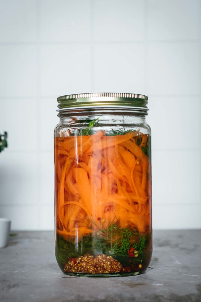 canning jar with carrot ribbons, dill, and other spices in brine