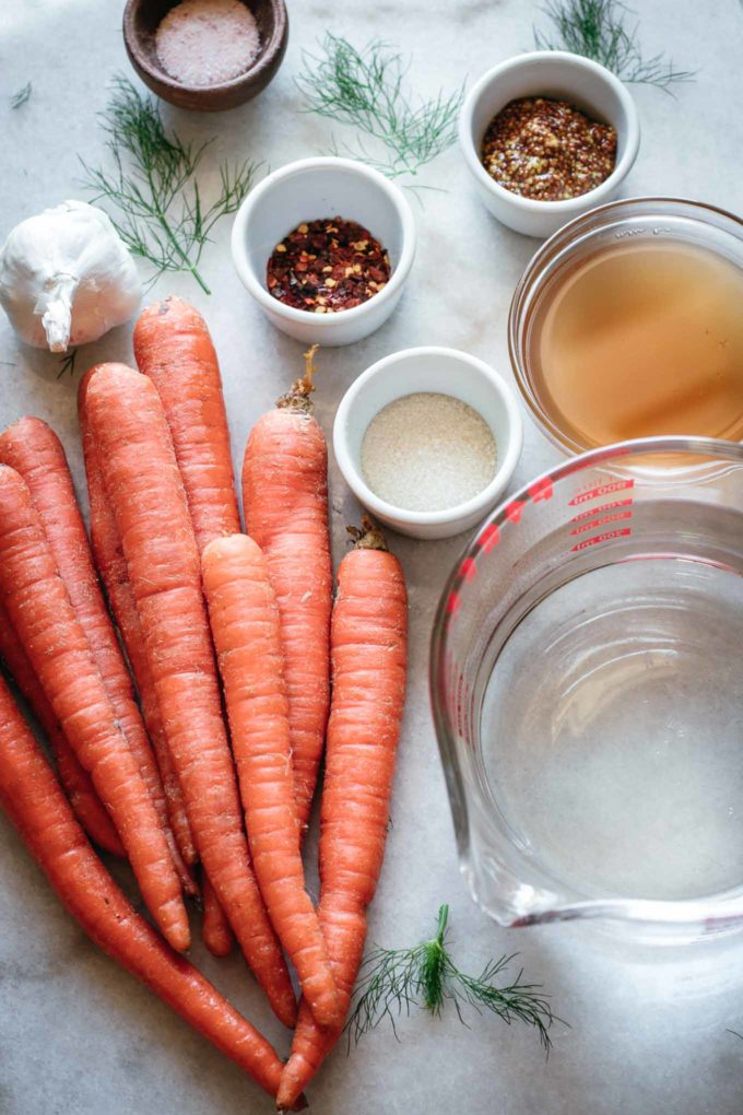 whole carrots and bowls of garlic, mustard seeds, red pepper flakes, salt, sugar, water and vinegar