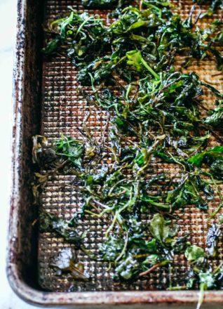 baked arugula leaves on a sheet pan