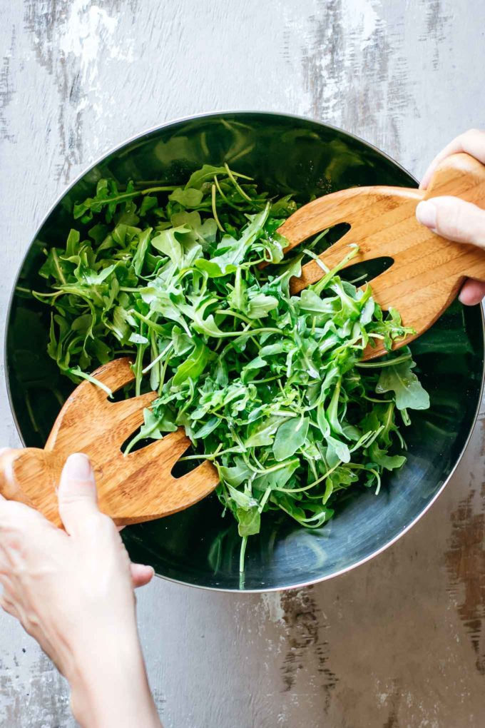 two hands tossing arugula with wooden spoons in a silver mixing bowl