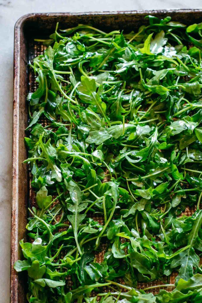 arugula leaves on a baking sheet before baking