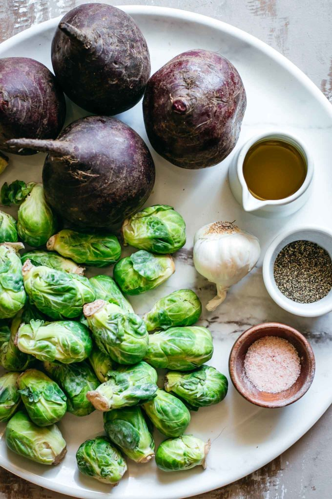 beets, brussels sprouts, garlic and bowls of oil, salt and pepper on a white platter