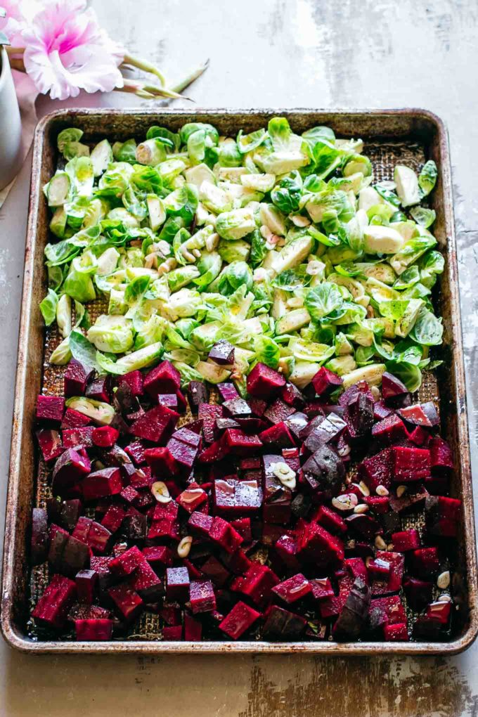 uncooked chopped beets and brussels sprouts on a baking pan