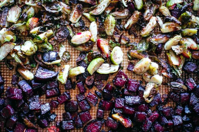 close up of roasted beets and brussels sprouts on a roasting pan after baking