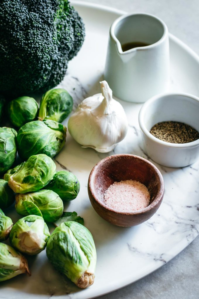 brussels sprouts, broccoli, garlic, and bowls of salt, pepper, and oil