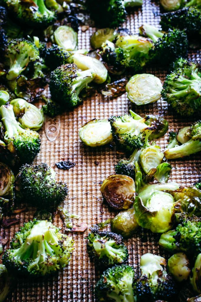 cooked broccoli and brussels sprouts on a baking sheet