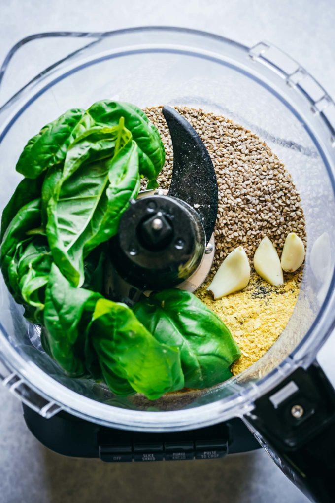 basil, sesame seeds, cheese, and garlic inside a food processor