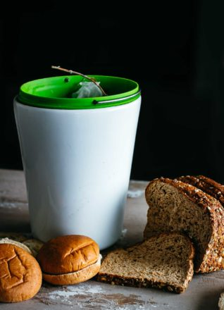 slices of bread and sliced buns next to a compost bin on a countertop