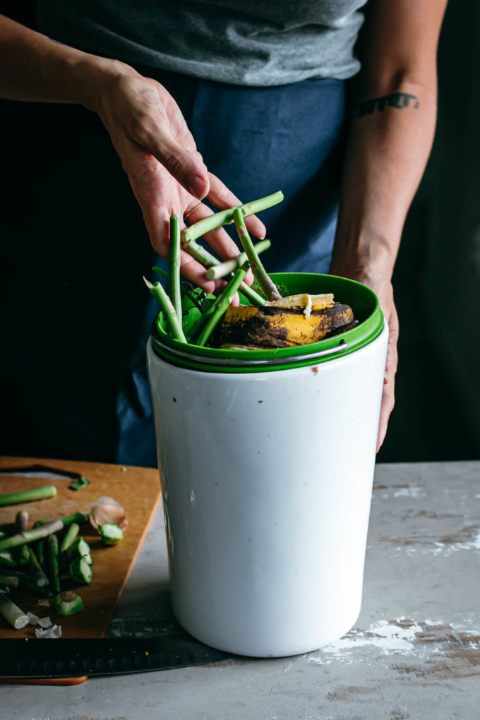 a hand pouring food scraps into a compost bin on a wood table