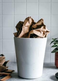 crumpled paper bag in a white ceramic bin on a countertop