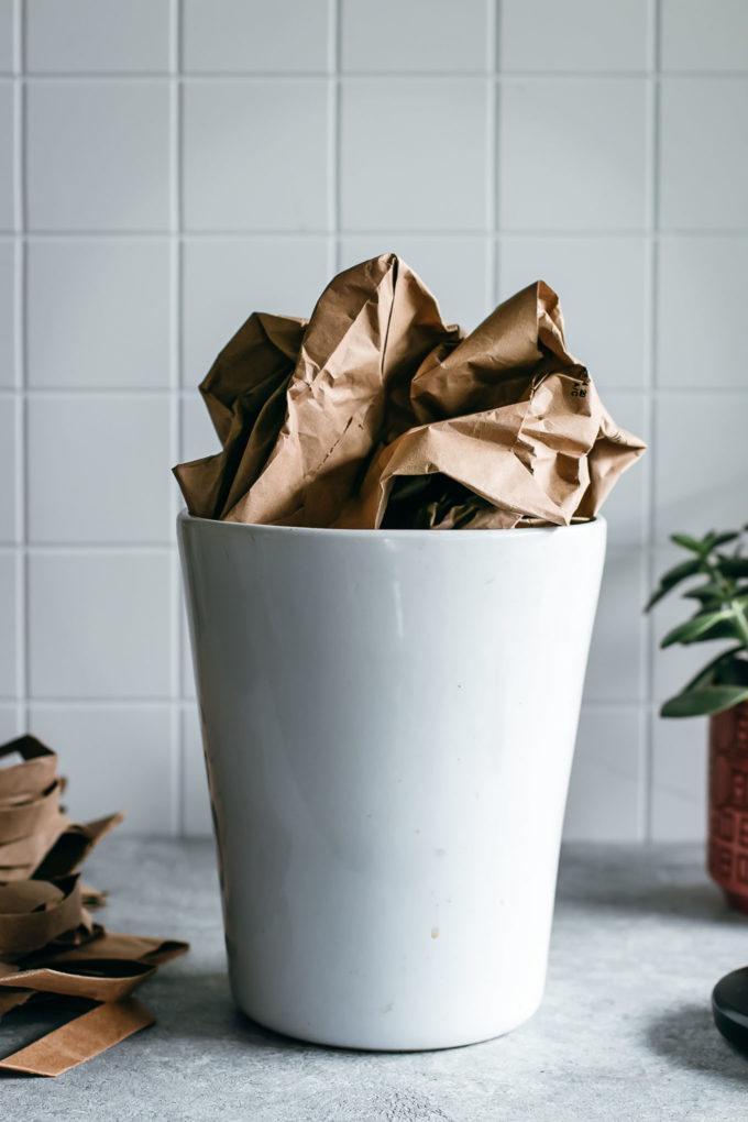crumpled paper bag in a white ceramic compost bin on a countertop