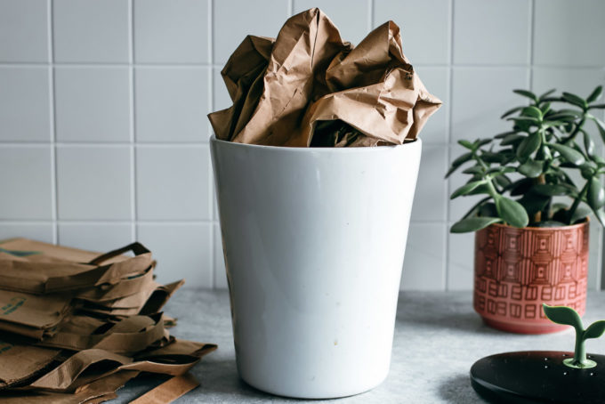 an old paper bag inside of a compost bin on a kitchen countertop