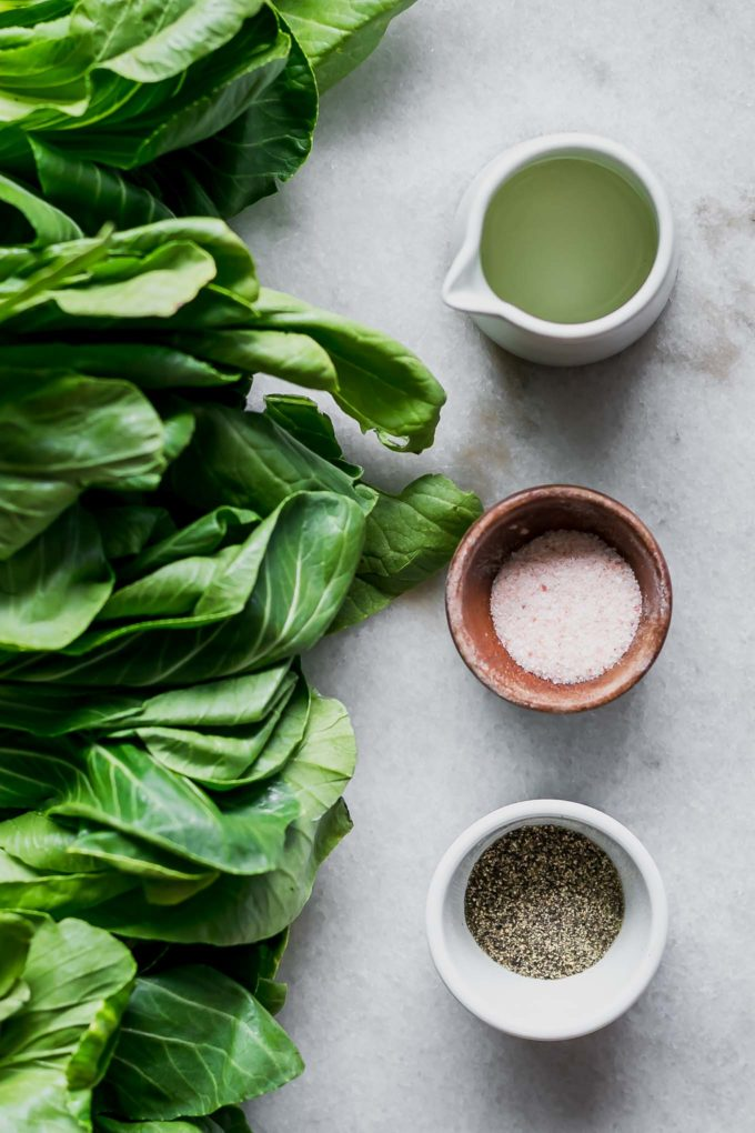 bok choy leaves and bowls of oil, salt, and pepper on a white countertop