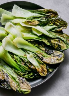 baked bok choy chips on a blue plate on a white table