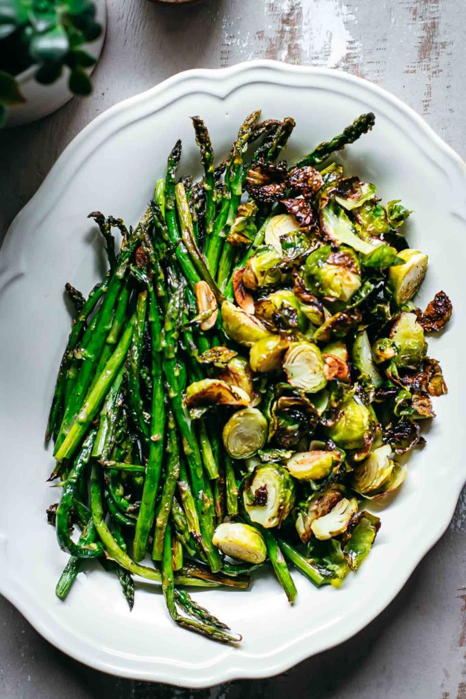 roasted brussels sprouts and asparagus in a white serving dish